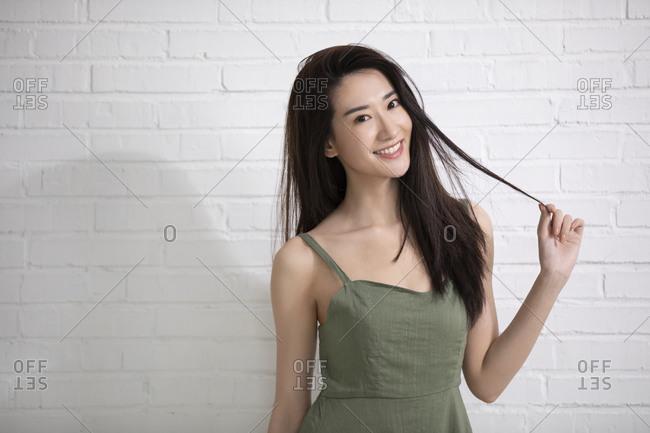Beautiful young Chinese woman wearing a green summer dress