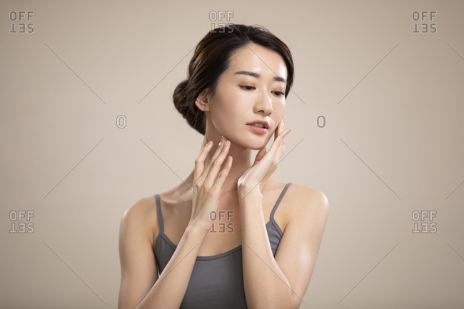 Beautiful young Chinese woman touching her face