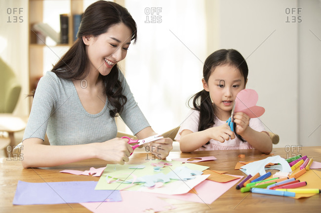 Happy Chinese mother and daughter cutting paper at home