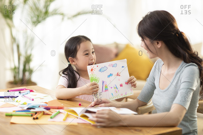 Happy Chinese mother and daughter drawing at home
