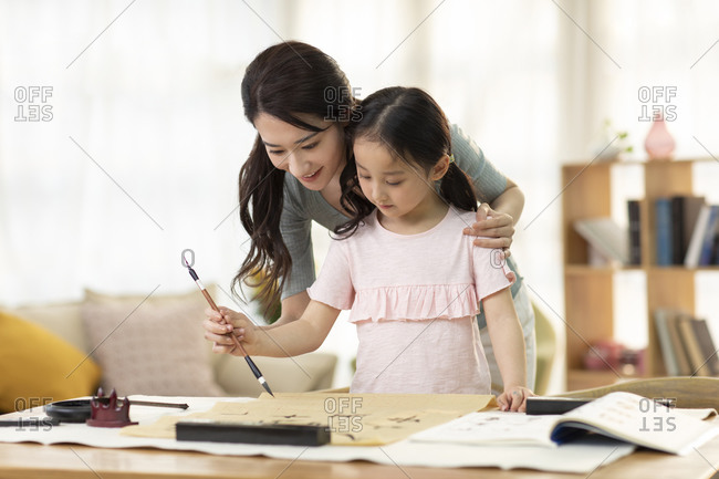 Happy Chinese mother and daughter writing calligraphy at home