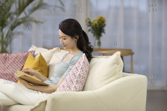Happy young Chinese woman reading book in living room