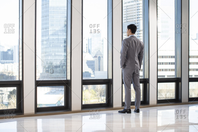 Young Chinese businessman looking through window
