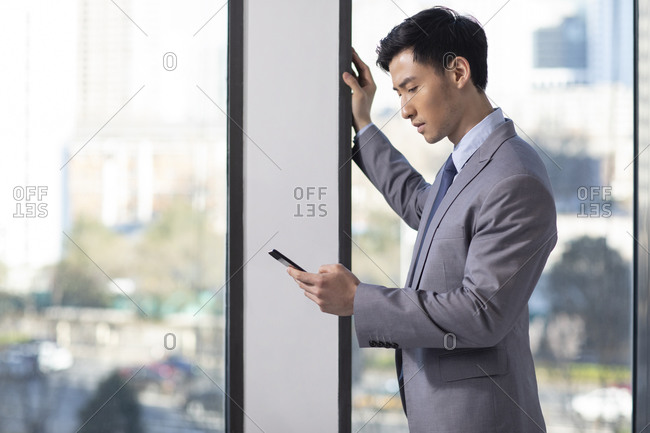 Young Chinese businessman using smartphone