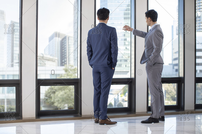 Successful Chinese businessmen talking by the windows