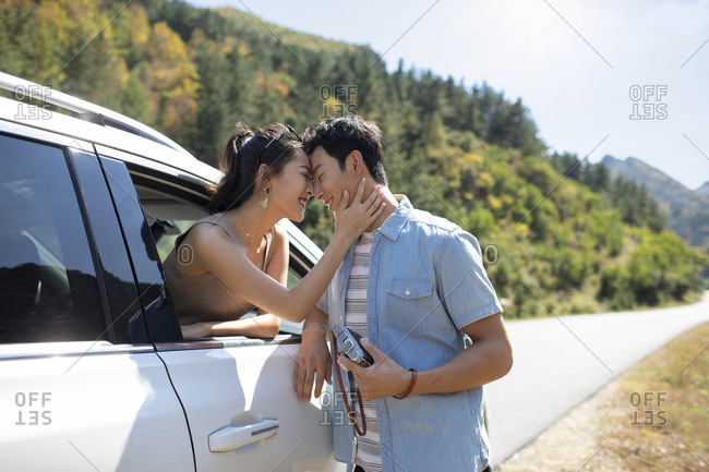 Happy young Chinese couple enjoying road trip