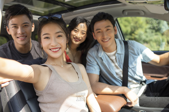 Happy young Chinese friends enjoying road trip