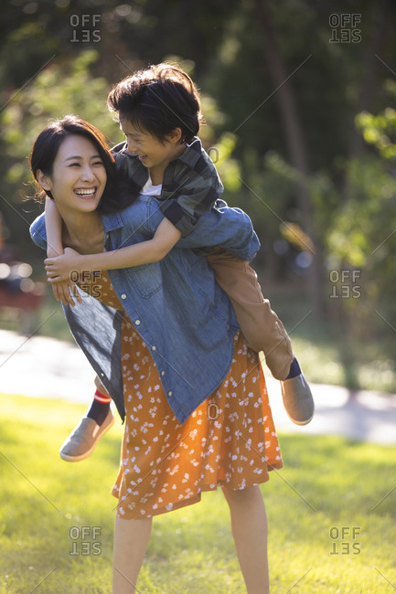 Happy Chinese mother and son playing in park
