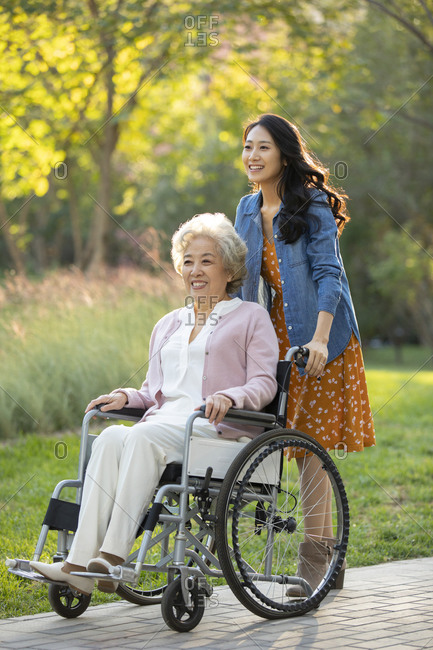 Happy Chinese mother and daughter relaxing in park