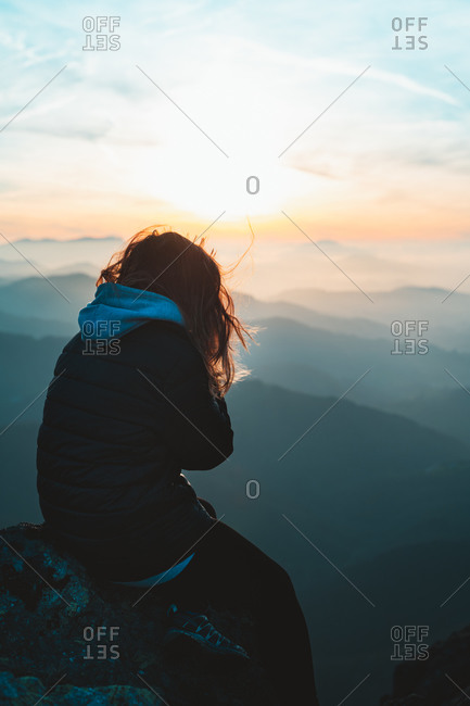 Young girl watching the sunset on top of a mountain after a hike