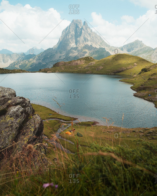 Two hikers setting their tents next to a picturesque lake in French Pyrenees
