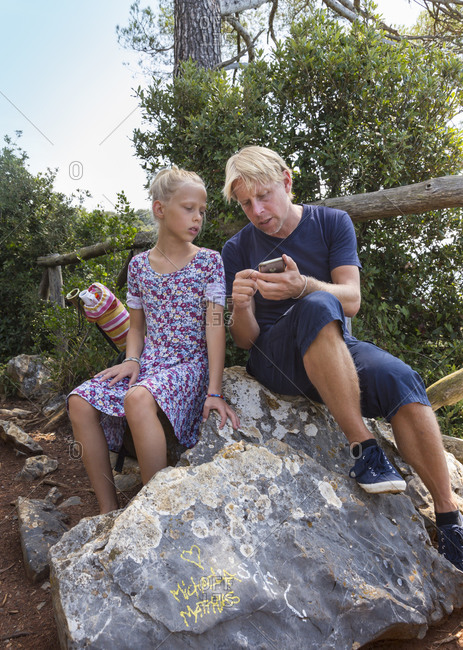 Girl and father sitting on rock looking at smartphone, Vernazza, Liguria, Italy