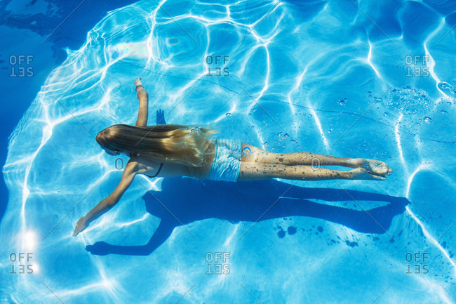 Girl swimming underwater in outdoor swimming pool, high angle view, Vernazza, Liguria, Italy