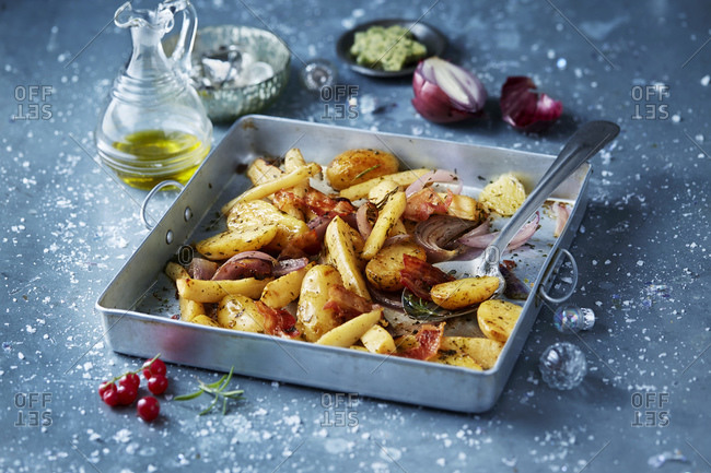 Roasted vegetables with red onions in roasting tin, seasonal christmas food