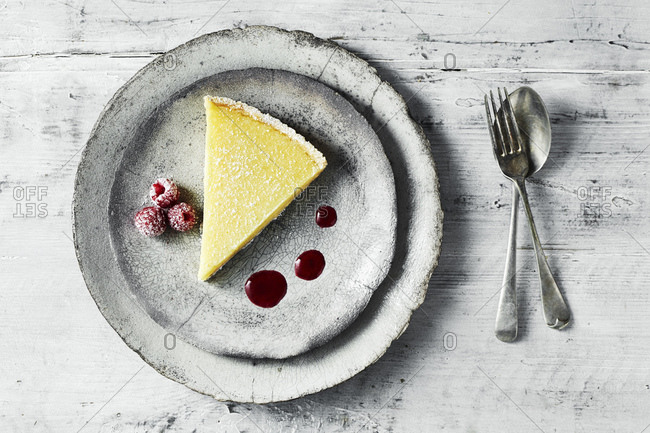 Still life with lemon tart and raspberries on plate, overhead view