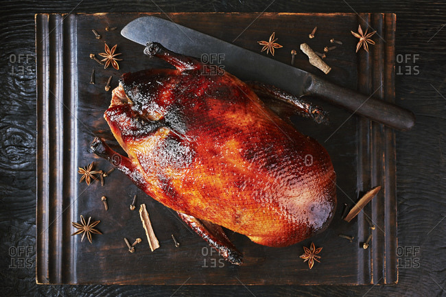 Still life with peking duck on cutting board, overhead view