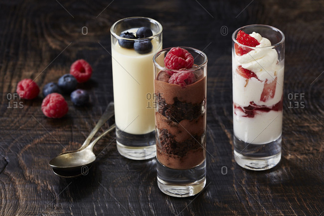 Still life with three desserts in glasses with raspberry and blackberry garnish