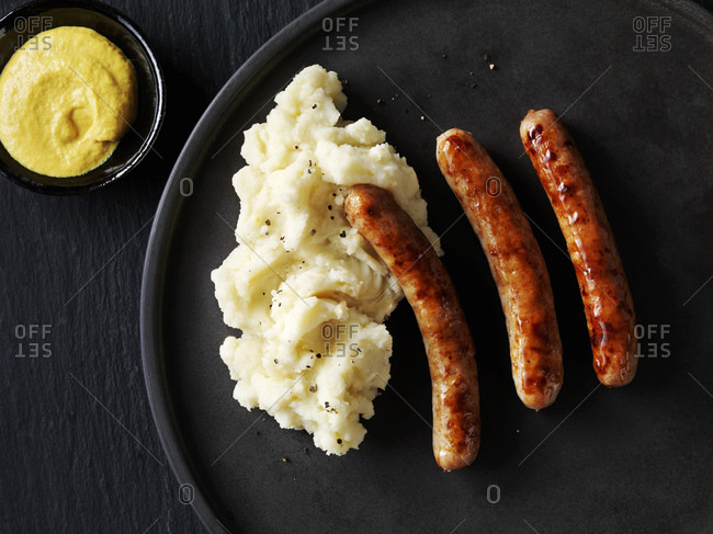 Still life with sausages and mash on black plate with bowl of  mustard, overhead view