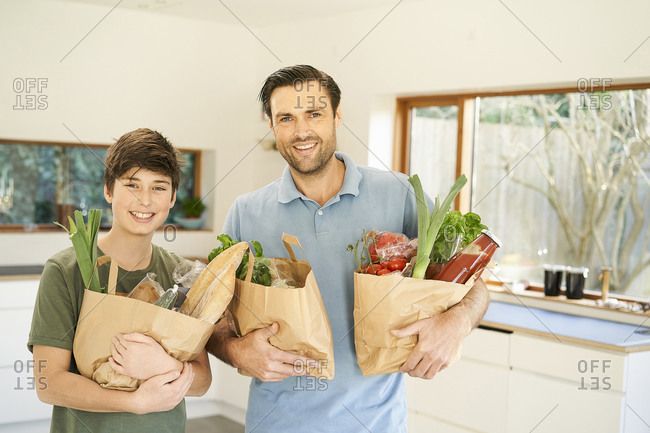 Boy and his father in kitchen holding grocery bags, portrait