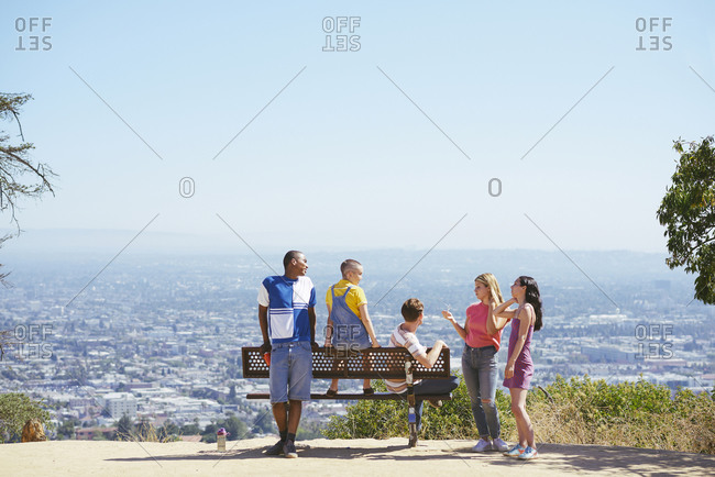 Five young adult friends on cityscape hilltop bench, rear view, Los Angeles, California, USA
