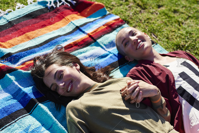 Two young female friends lying on picnic blanket in park, Los Angeles, California, USA