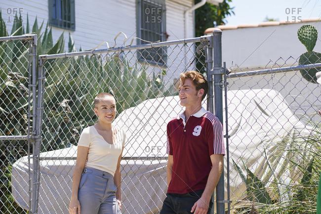 Young man and teenage girl on suburban sidewalk, Los Angeles, California, USA