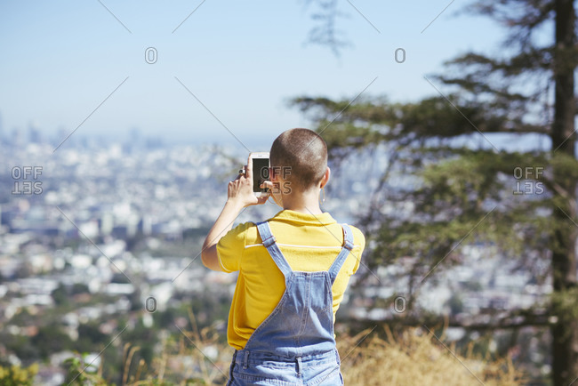 Teenage girl photographing view from cityscape hilltop, Los Angeles, California, USA