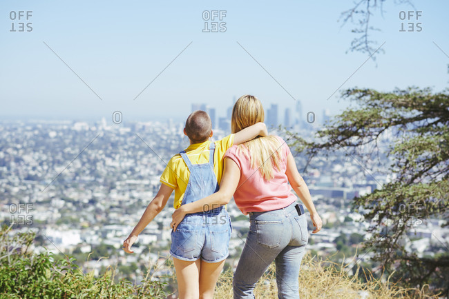 Two young female friends looking at skyline from hilltop, rear view, Los Angeles, California, USA