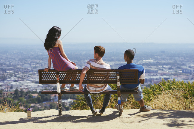 Three young adult friends looking out at cityscape from hilltop bench, rear view, Los Angeles, California, USA