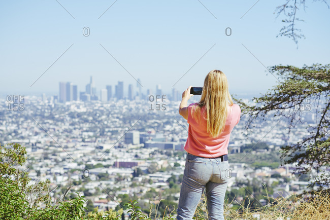 Young woman photographing skyline from hilltop, rear view, Los Angeles, California, USA