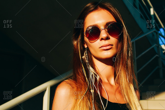 Young woman with long brown hair and sunglasses on stairway, head and shoulder portrait