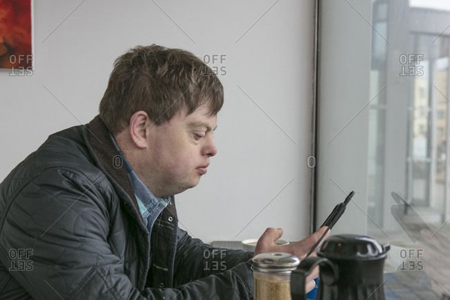 Man with down syndrome using phone by cafe window