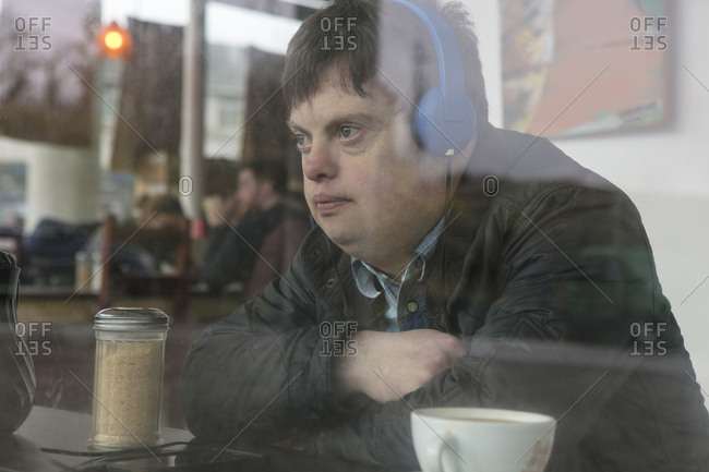 Man with down syndrome using headphones by cafe window