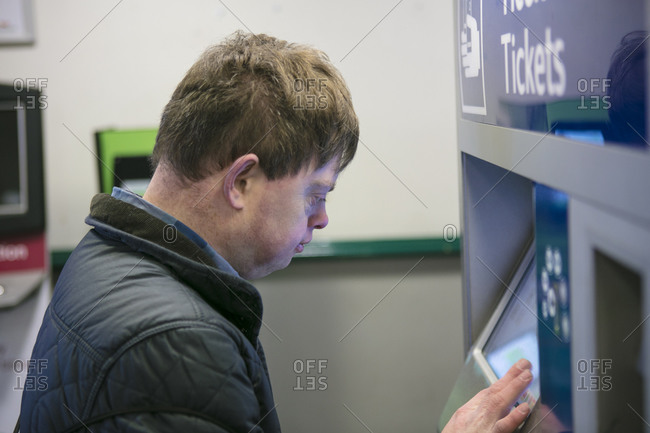 Man with down syndrome at train ticket machine, Galway, Ireland