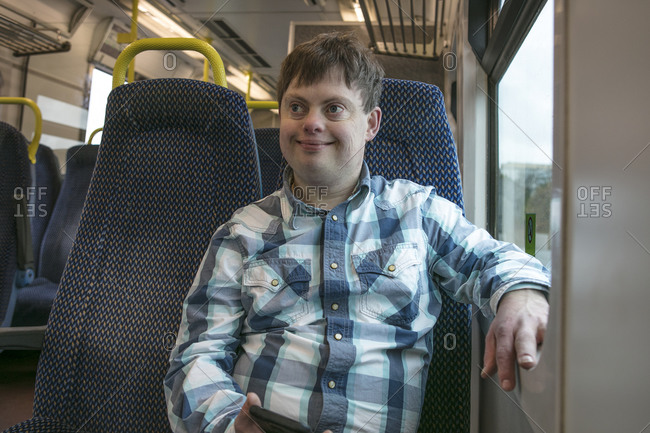 Man with down syndrome with cell phone on train