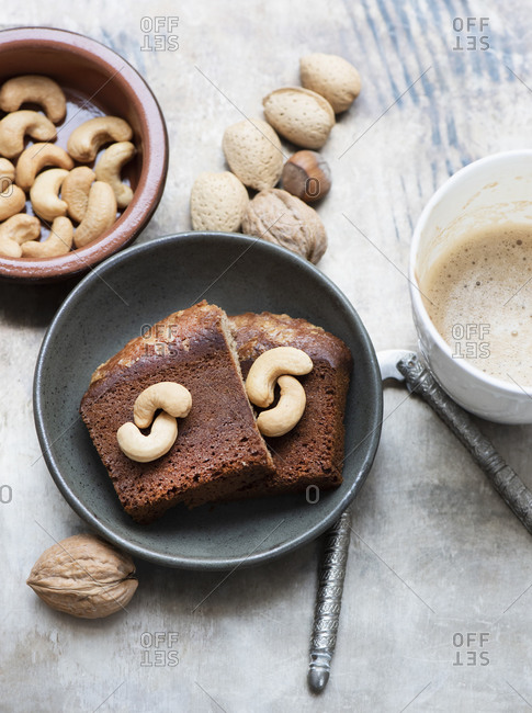 Walnuts in shell, cashew nuts, cake slices and coffee