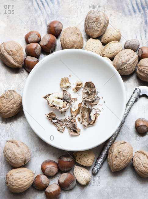 Walnuts and almonds in shell, hazelnuts, cracked walnut in bowl