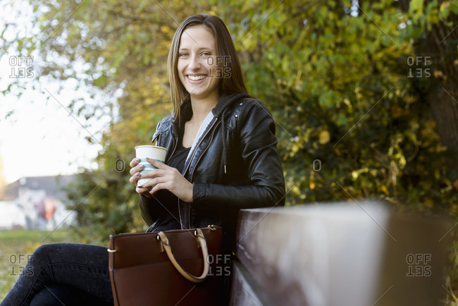 Young woman on coffee break in park