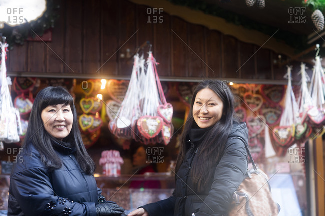 Mother and daughter window shopping at Christmas market, Freiburg, Baden-Wurttemberg, Germany