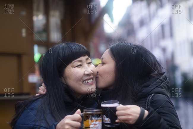 Mother and daughter drinking at Christmas market, Freiburg, Baden-Wurttemberg, Germany