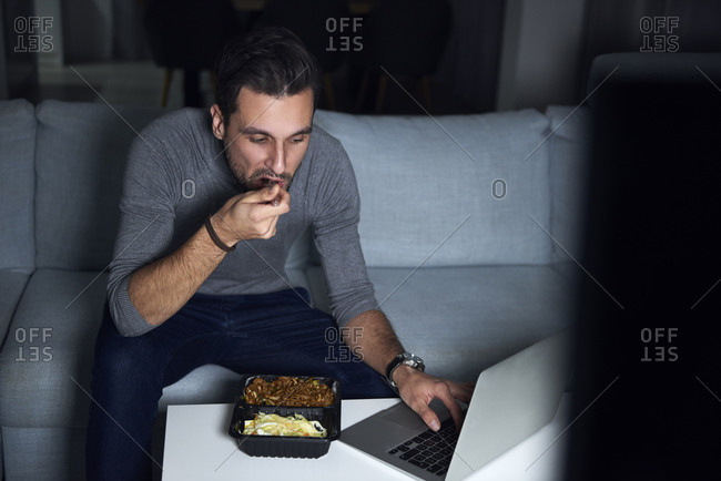 Young man sitting on sofa in evening eating takeaway and using laptop