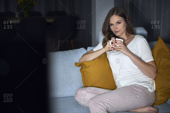Young woman sitting on sofa in evening watching TV