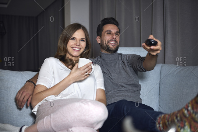 Young couple sitting on sofa in evening watching TV