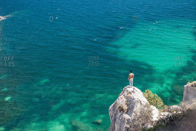 Young man looking out from coastal rock, Cagliari, Sardinia, Italy