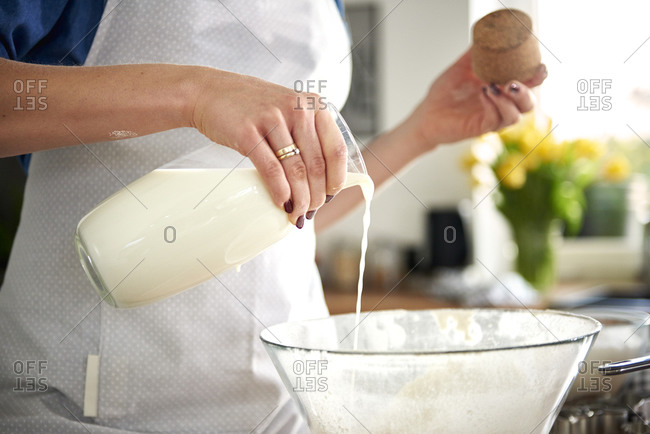 Woman pouring milk into mixing bowl in kitchen