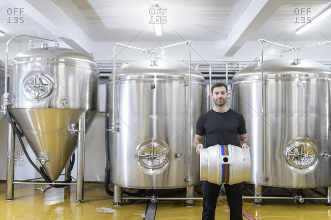 Portrait of brewer with barrel in small brewery