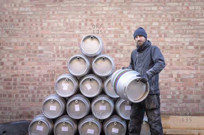 Portrait of brewer by stack of barrels in small brewery