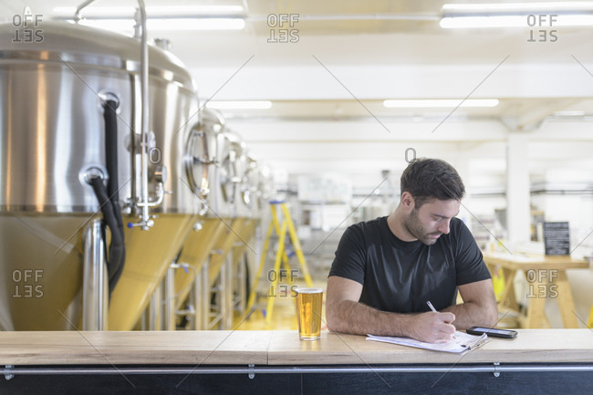 Brewer ordering ingredients on phone in small brewery