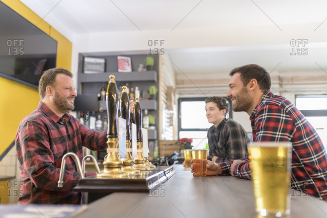 Customers and server drinking beer in small brewery
