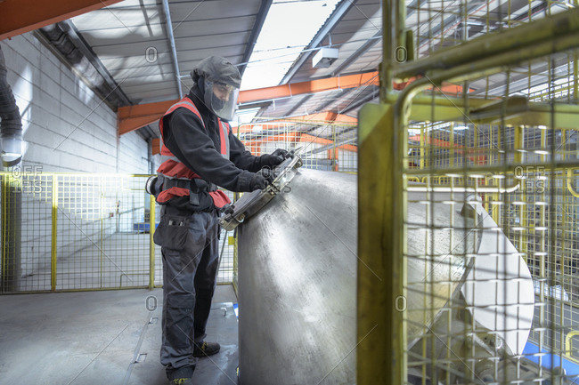 Worker mixing recycled metals from catalytic converters in recycling factory